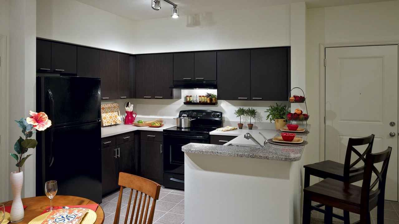 kitchen with track lighting and dark cabinetry