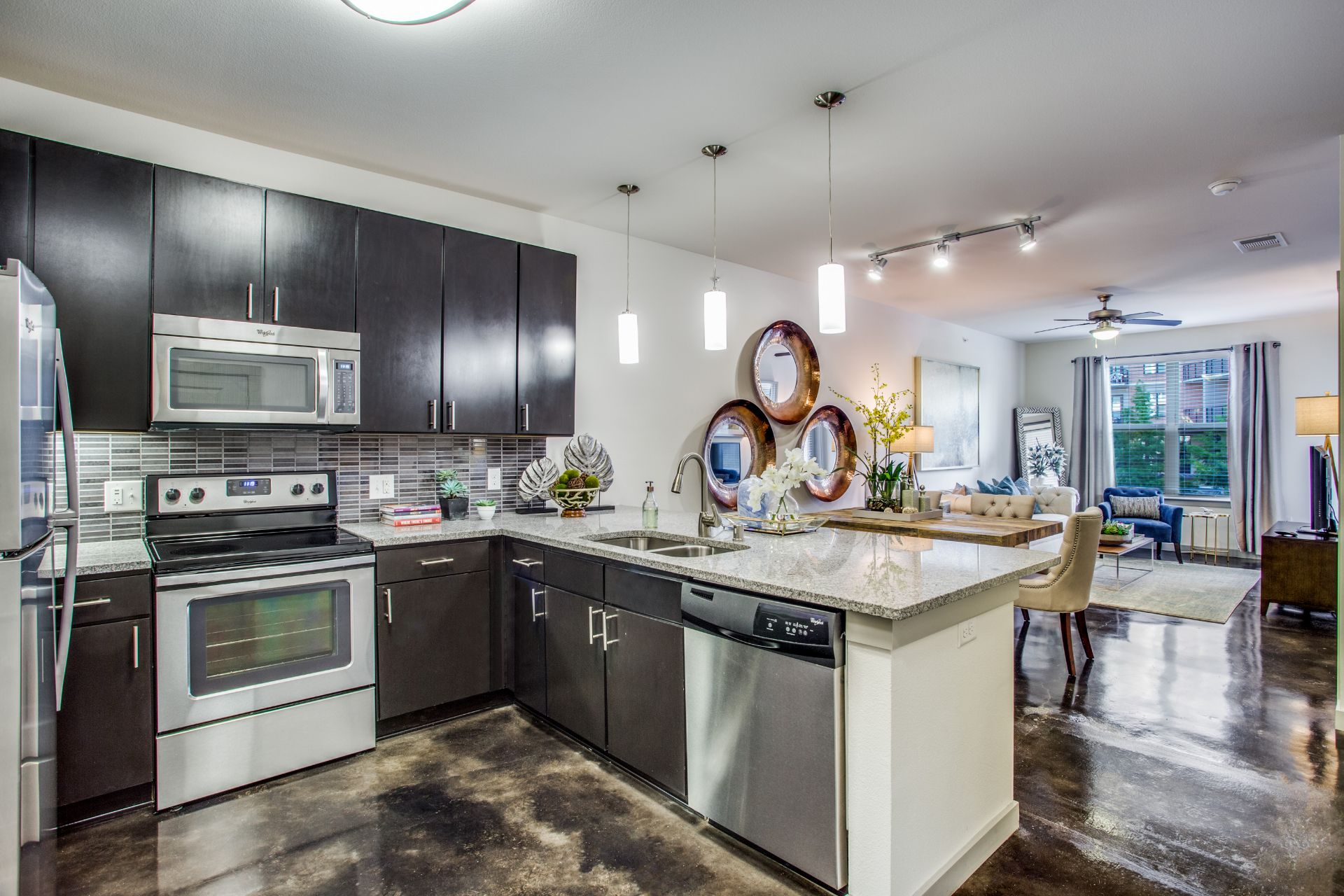 Apartment kitchen with stainless steel appliances and dark cabinetry
