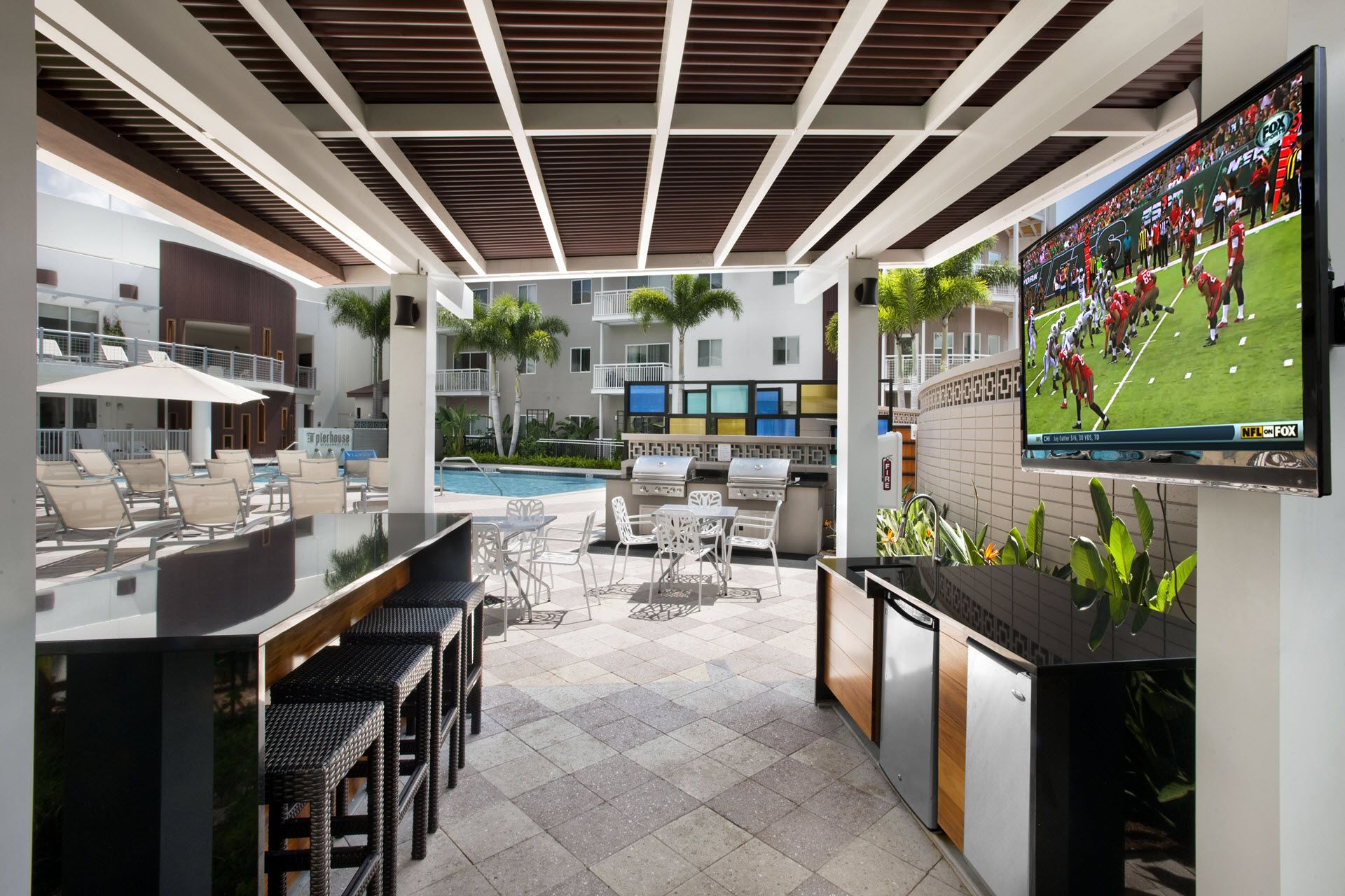 Outdoor kitchen with bar and television