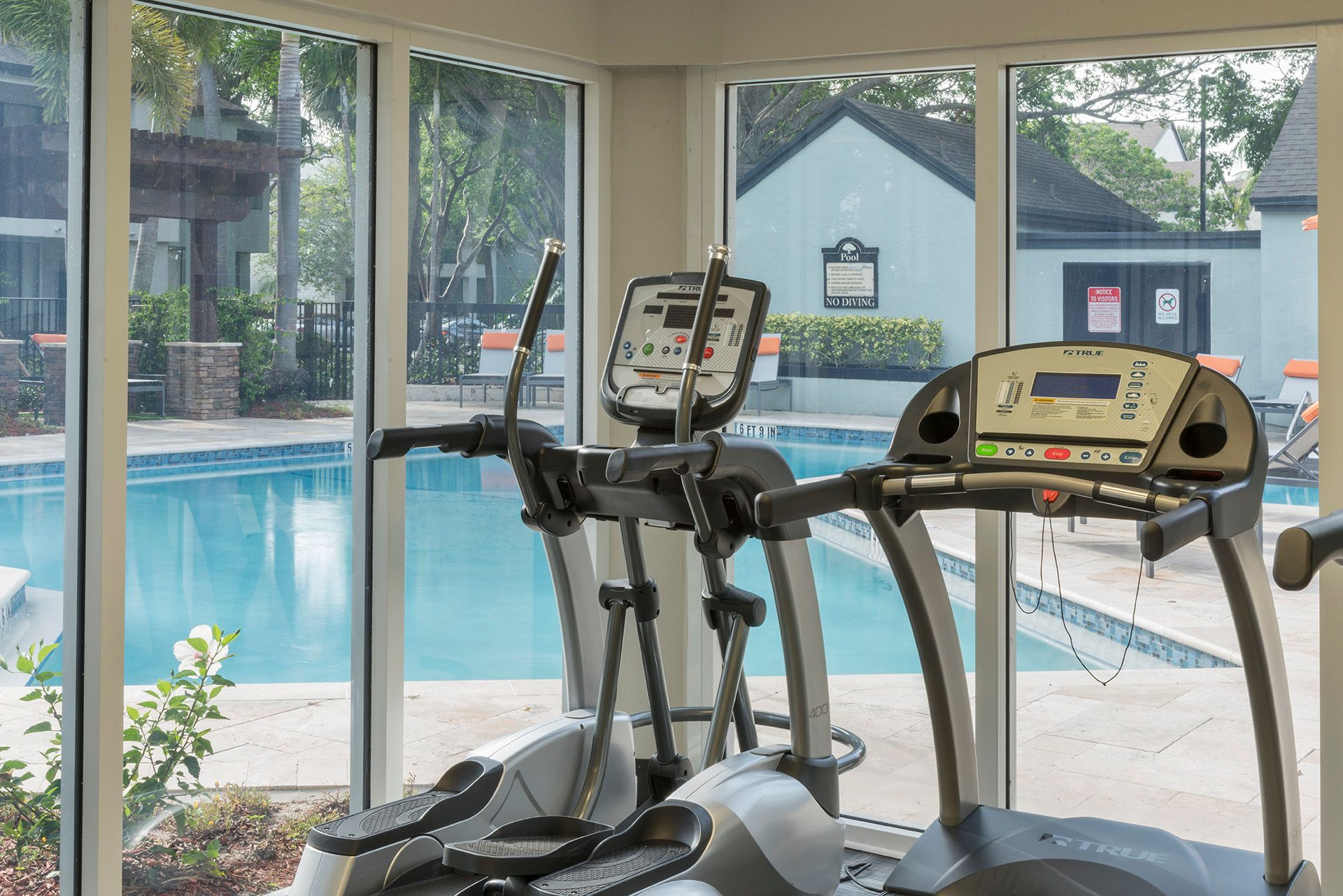 Fitness center overlooking swimming pool