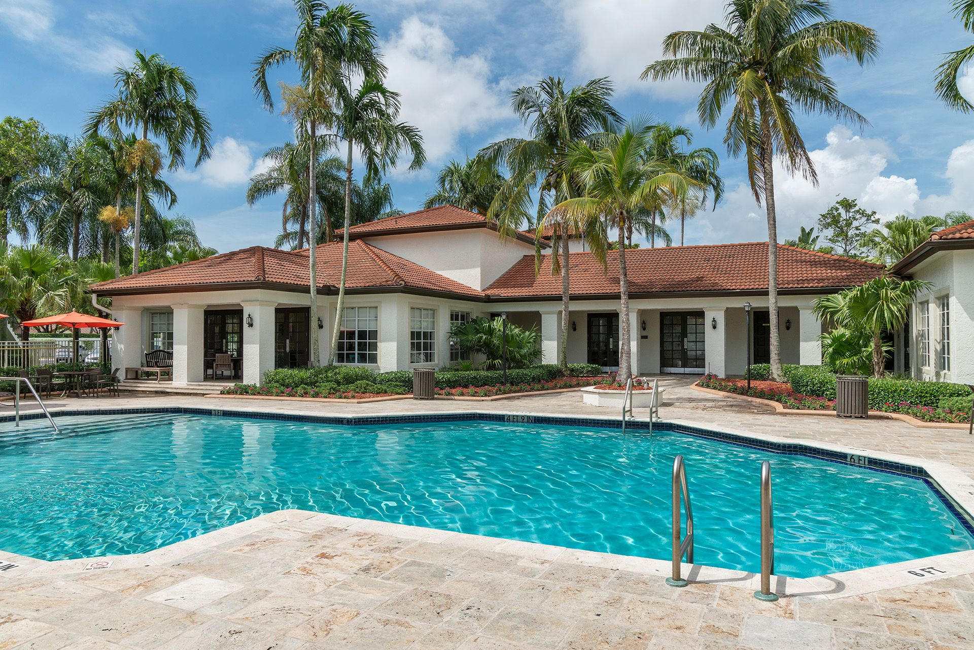 Pool and clubhouse with palm trees