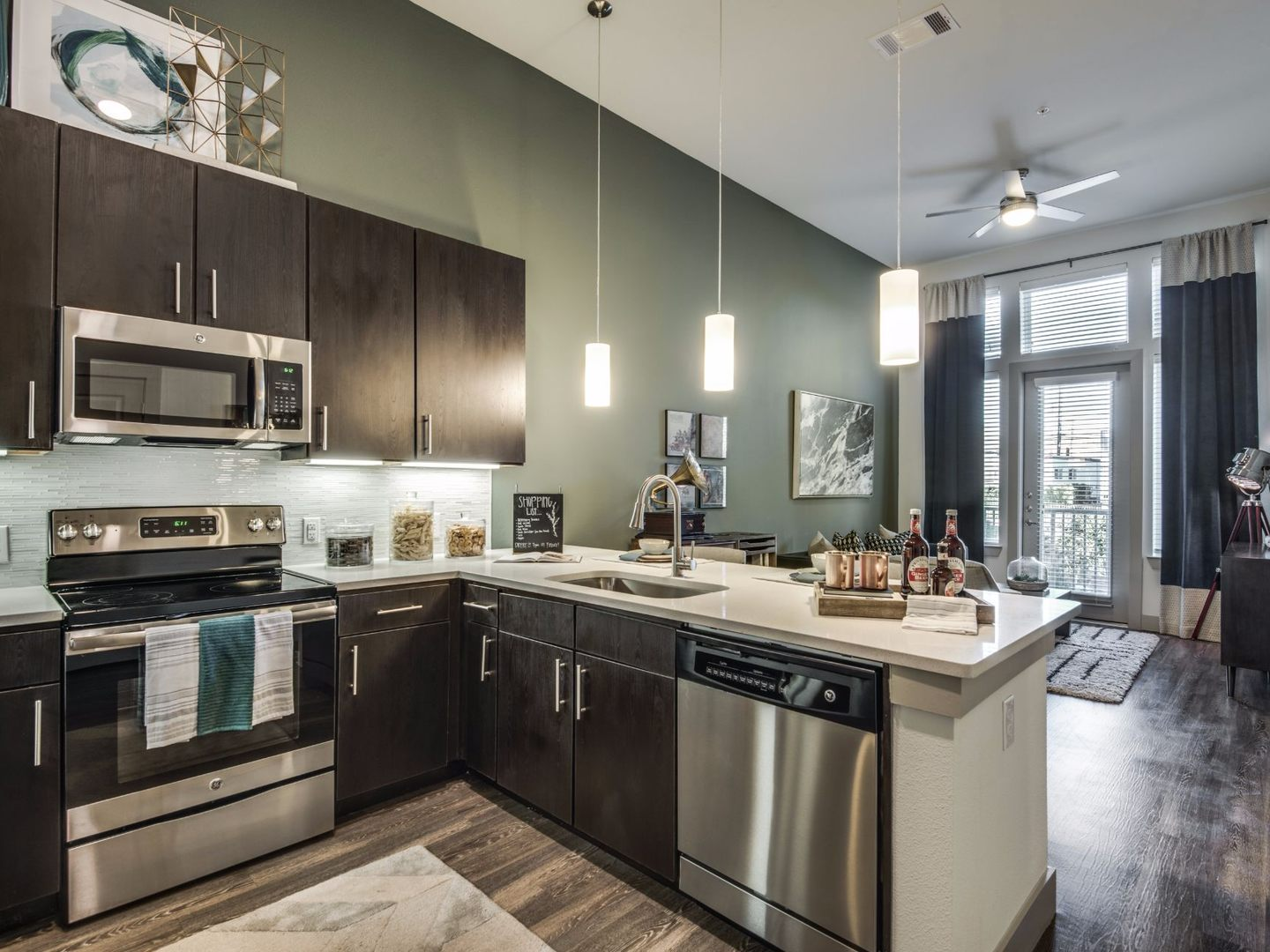Apartment kitchen with stainless steel appliances and view of living room