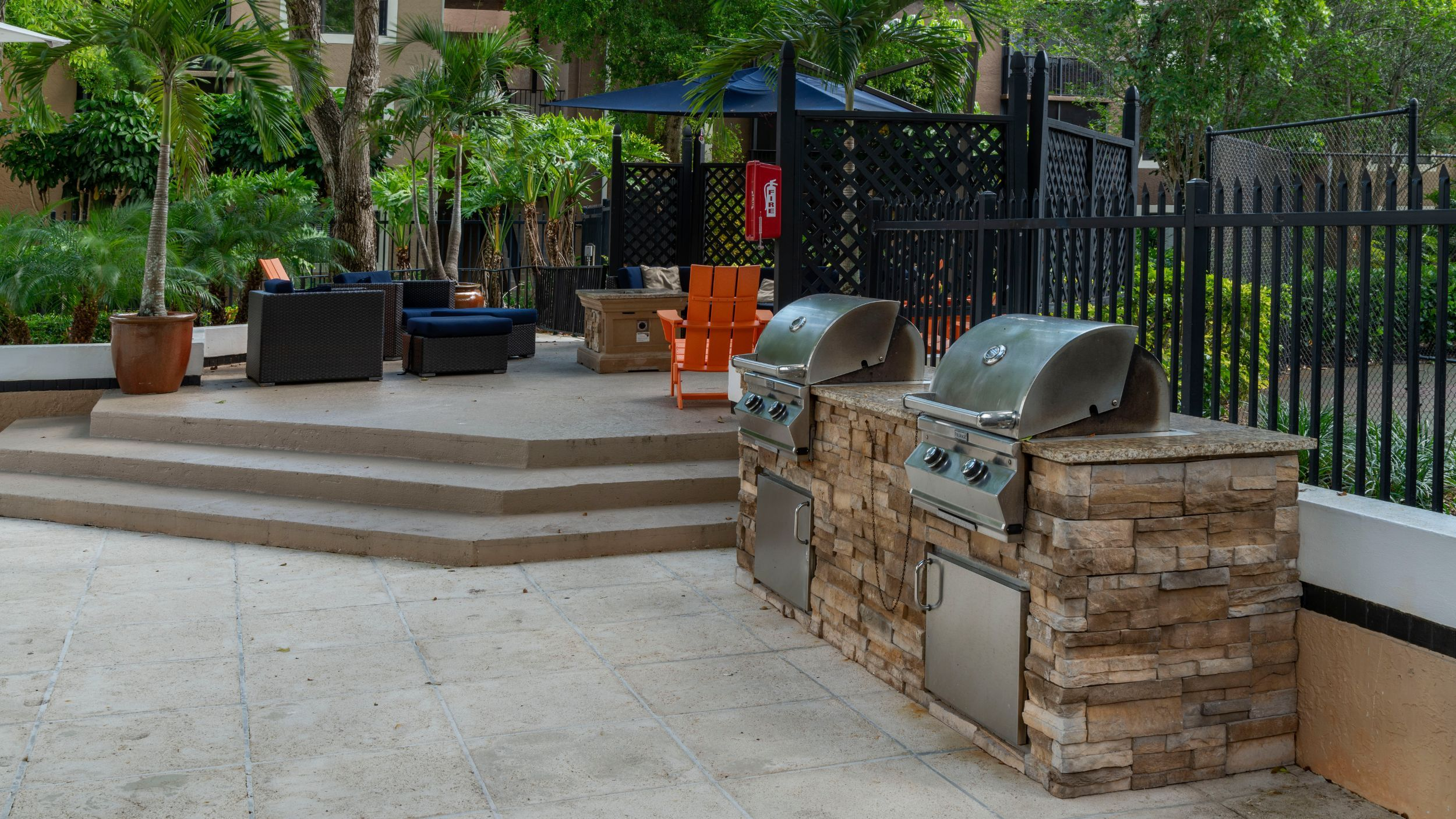 Outdoor lounge area with seating and grills