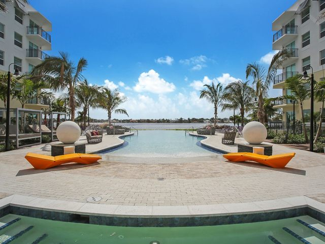 Resort style pool with lounge chairs and tables
