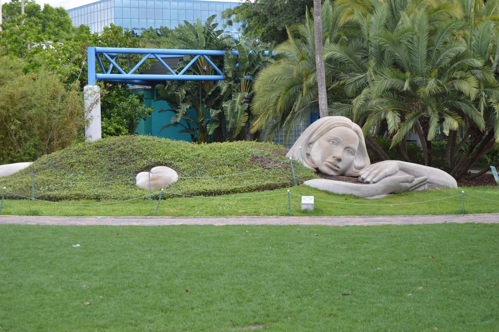 Statue of giant woman laying under blanket of earth