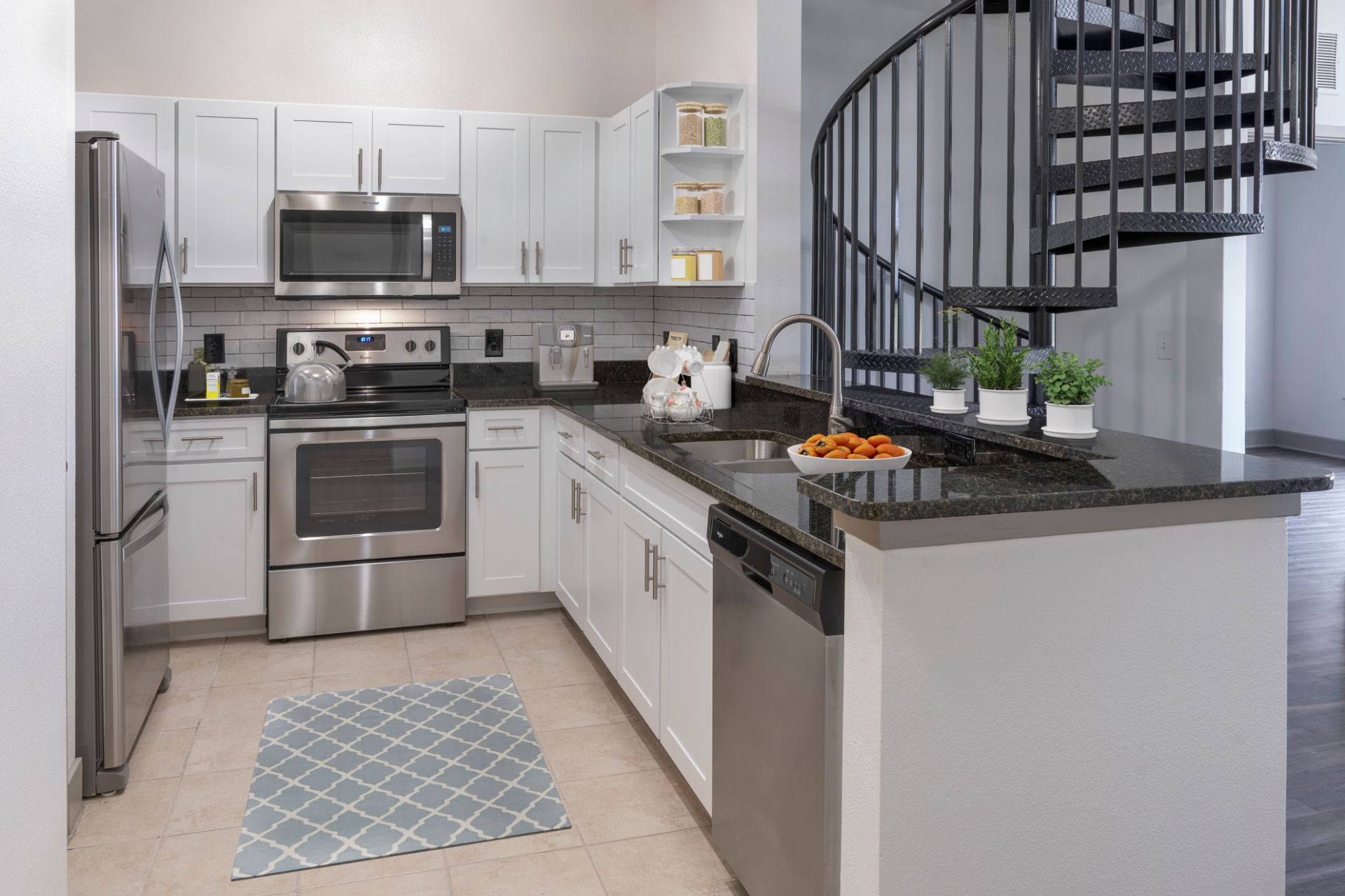 Apartment kitchen with stainless steel appliances and view of staircase