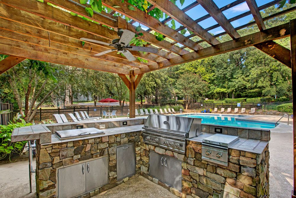 Outdoor grills under cabana with view of swimming pool