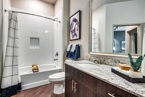 Soaking tub with tile and vanity with granite counter in apartment bathroom