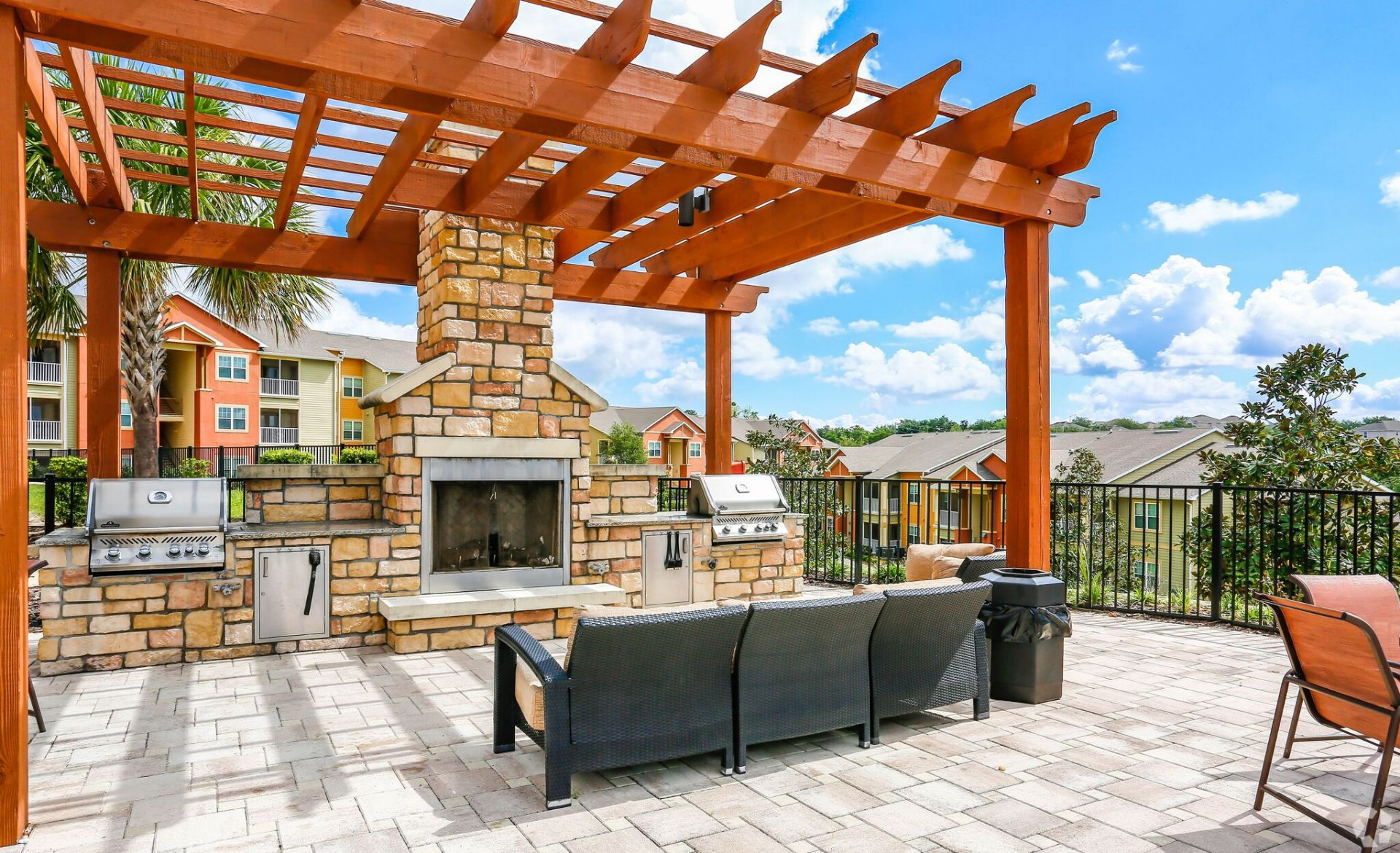 Outdoor lounge area with seating, grills, and fireplace