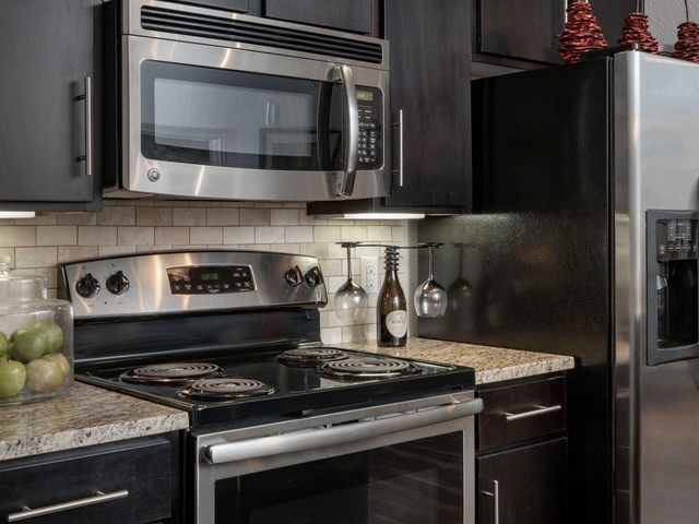 Apartment kitchen with granite countertops and stainless steel appliances