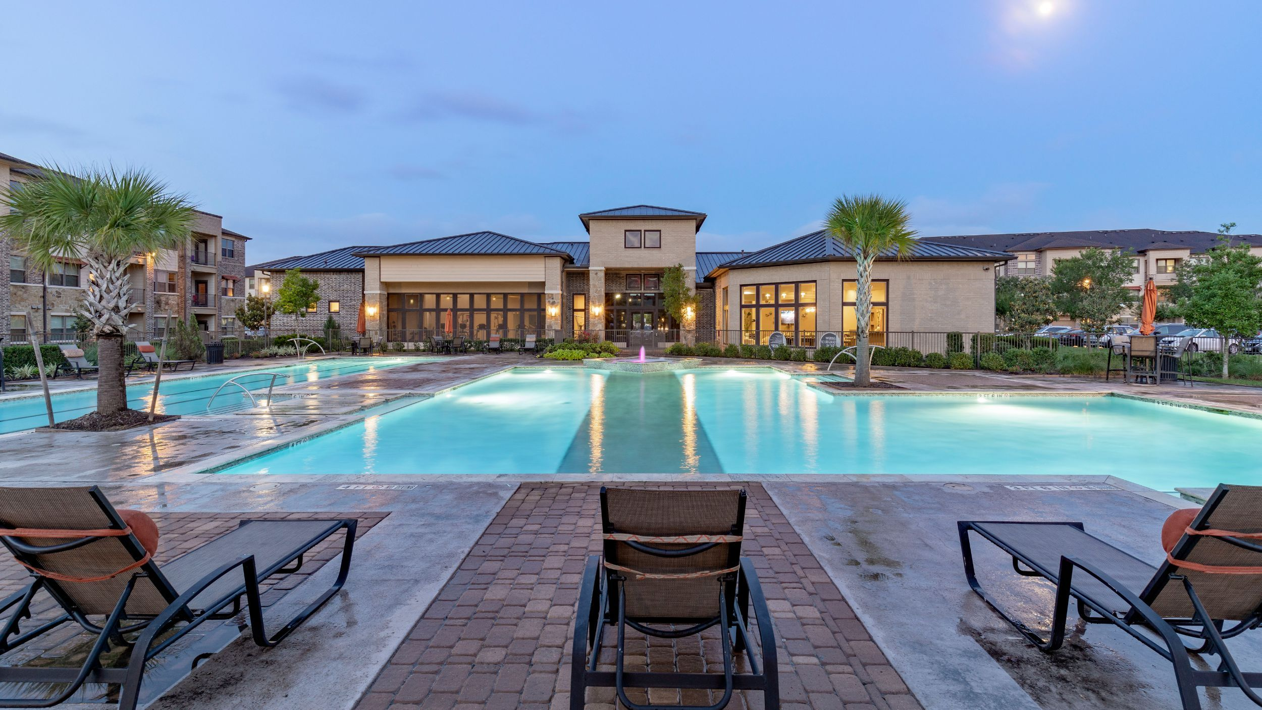 Swimming pool area with seating and view of clubhouse