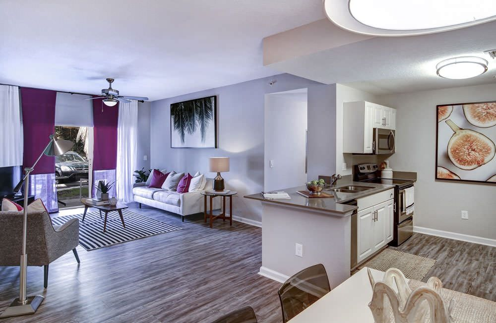 View of apartment kitchen and living room with hardwood-style plank flooring