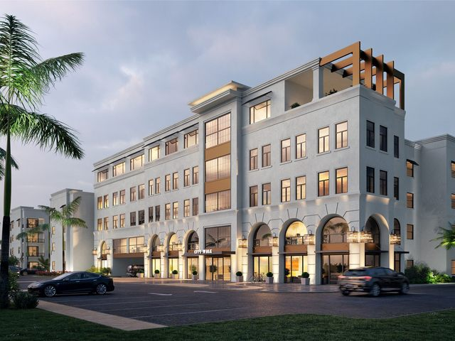 Building exterior with open parking and palm trees.