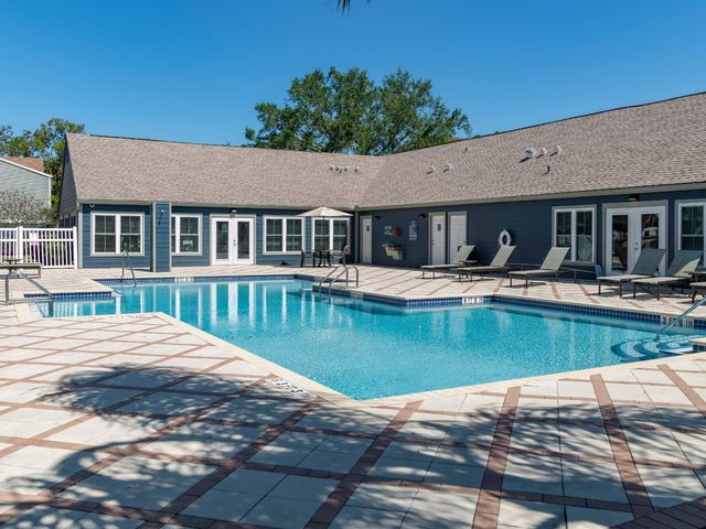 Swimming pool with seating and exterior view of clubhouse