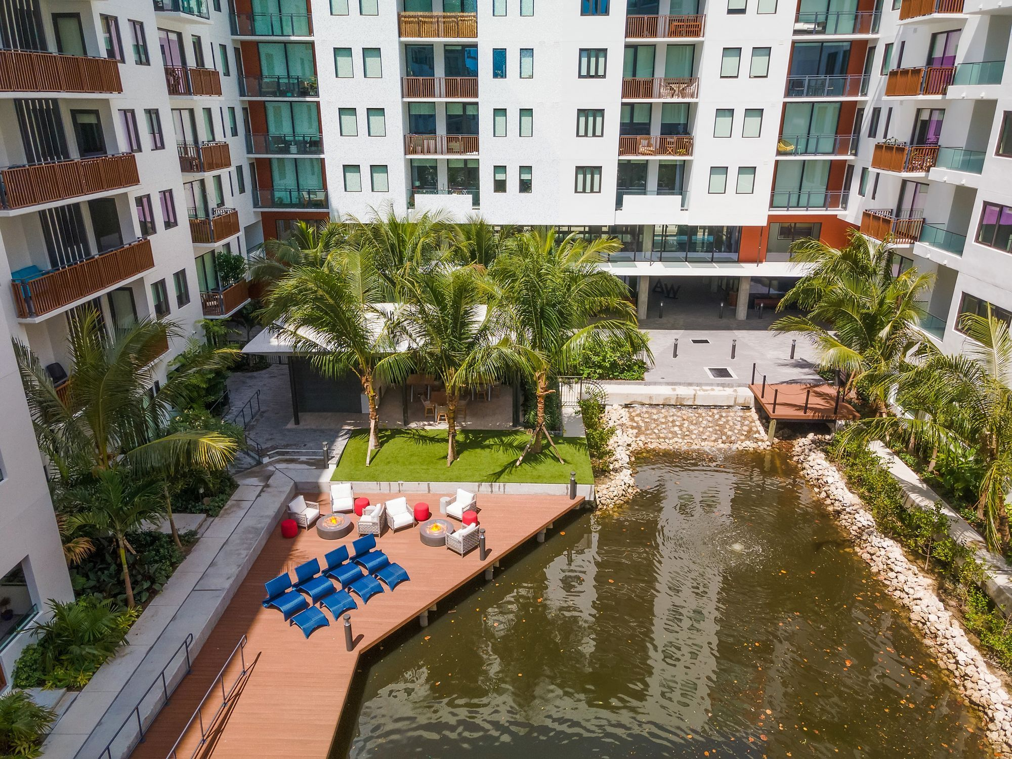 Marina area with seating, fire pit, and view of water and apartment buildings
