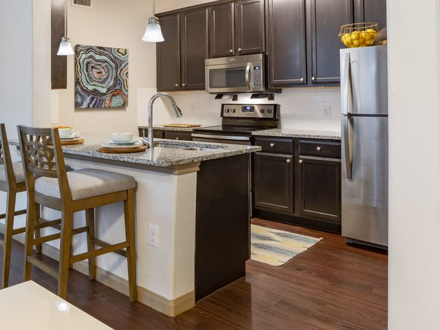 Apartment kitchen with stainless steel appliances and bar area with seating