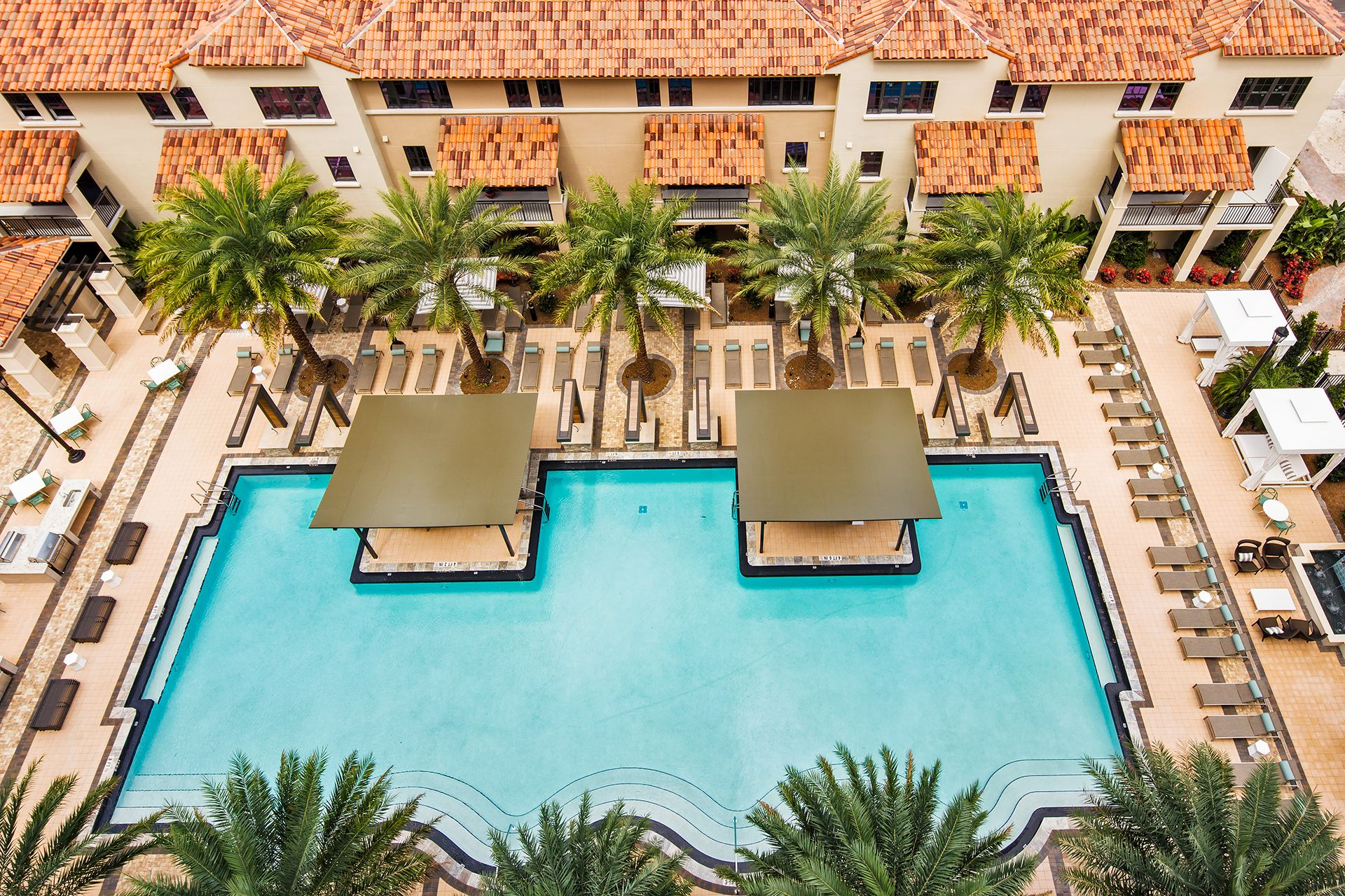 Aerial view of swimming pool with seating and cabanas