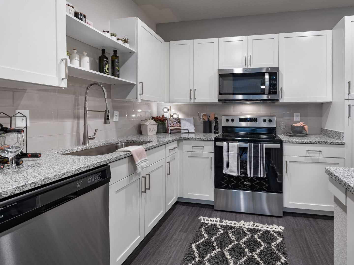 Apartment kitchen with stainless steel appliances and granite countertops