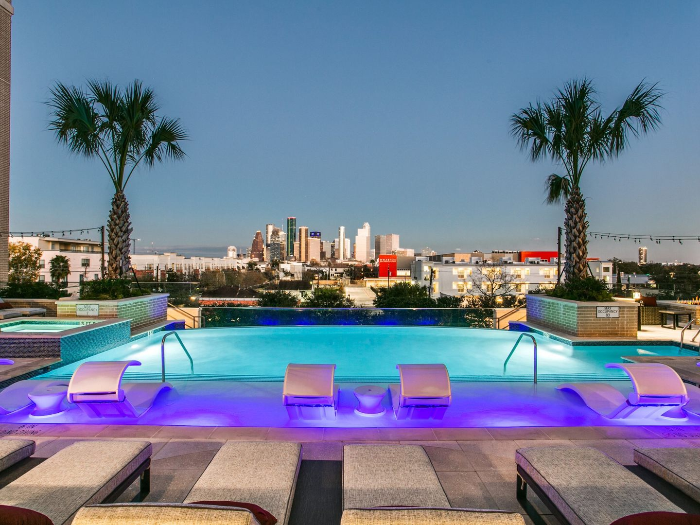 Swimming pool with seating and tanning ledge and view of city