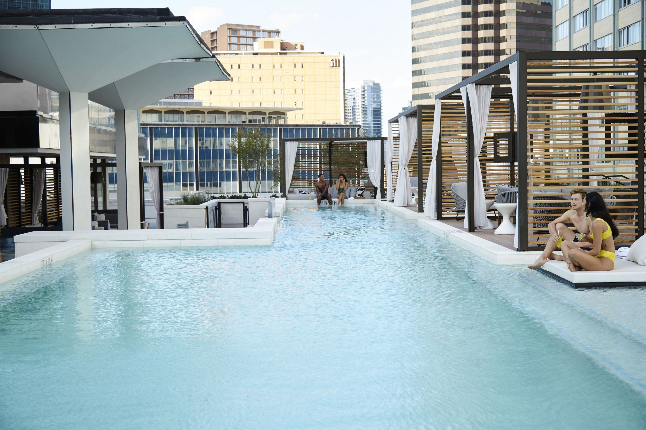 Rooftop swimming pool with seating and cabanas