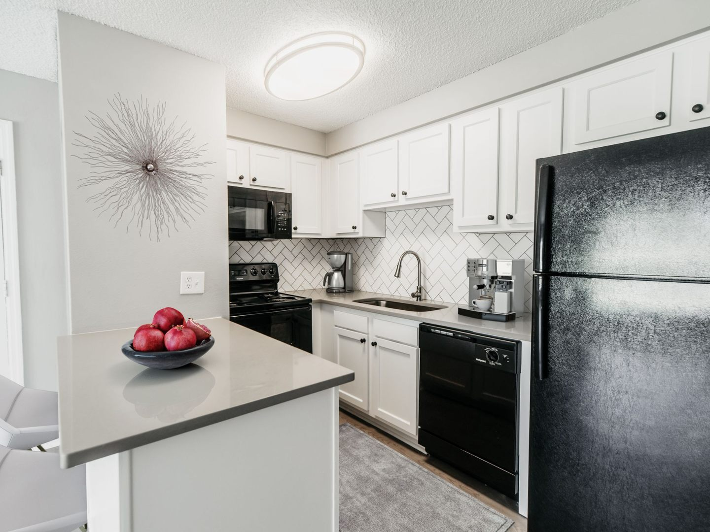 Apartment kitchen with black appliances and white cabinetry