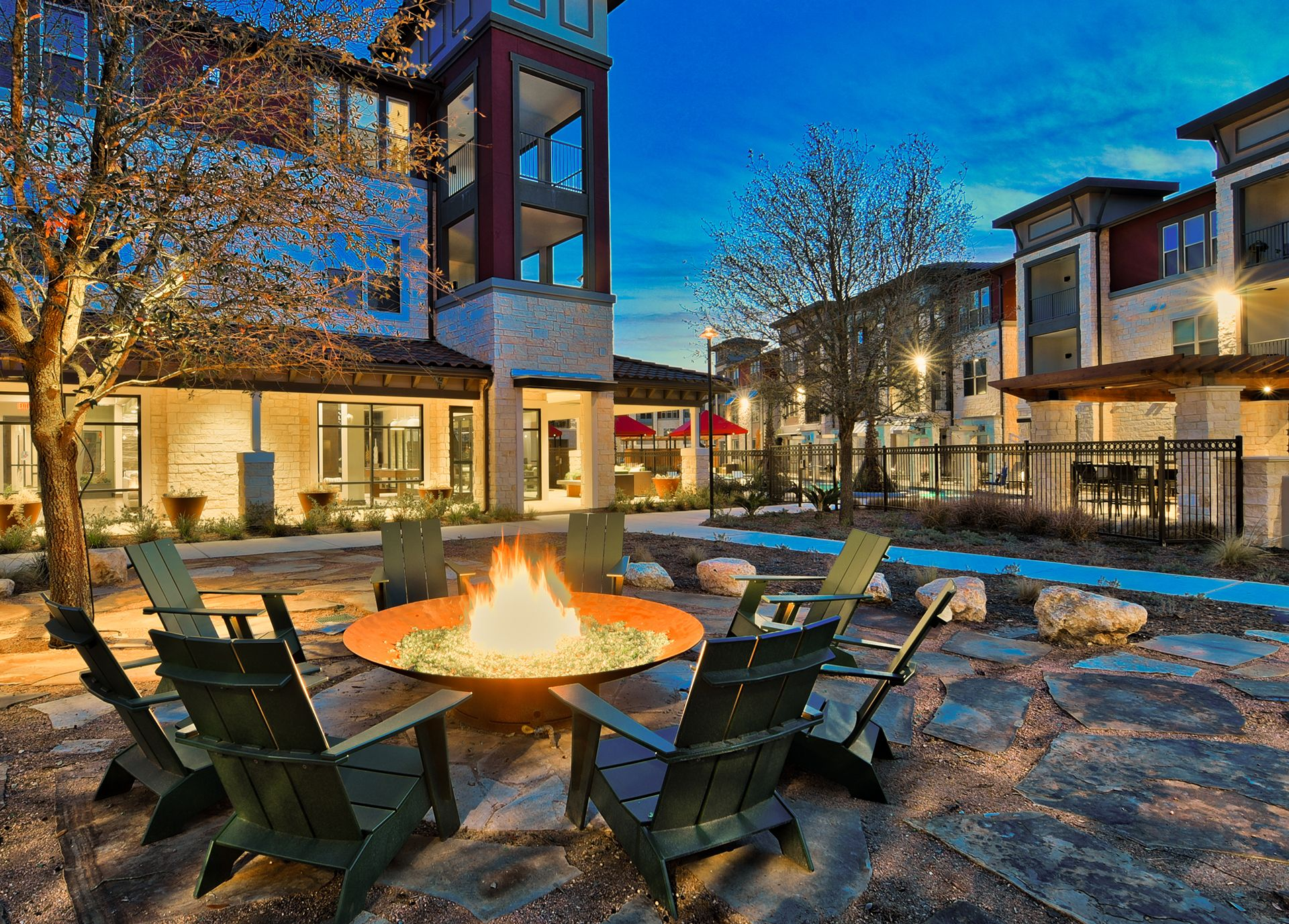 outdoor fire pit with seating and view of pool