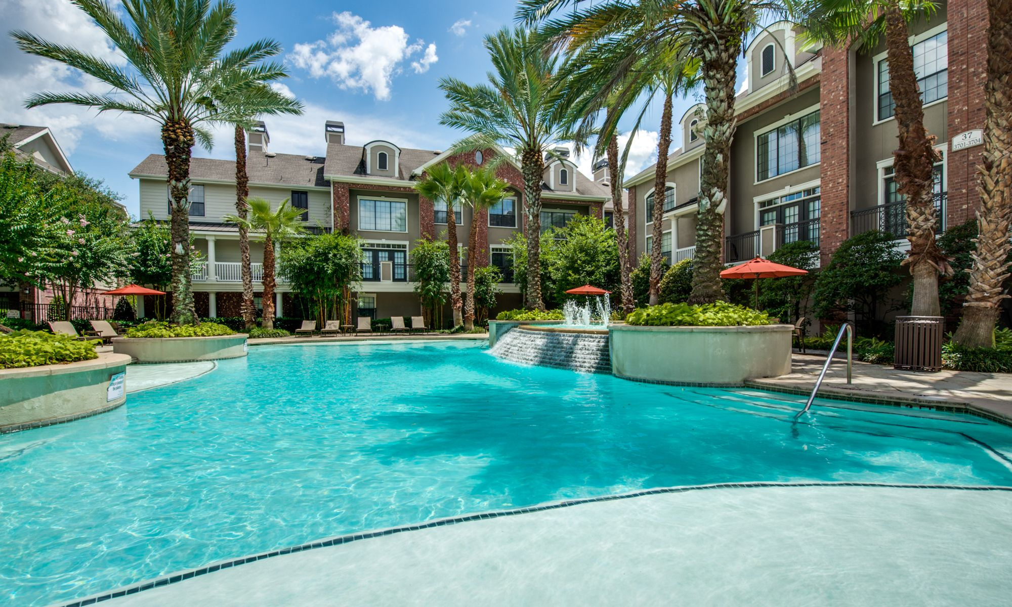 pool surrounded by palm trees and apartment buildings