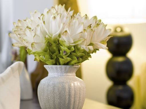 White vase with flowers on dark colored table