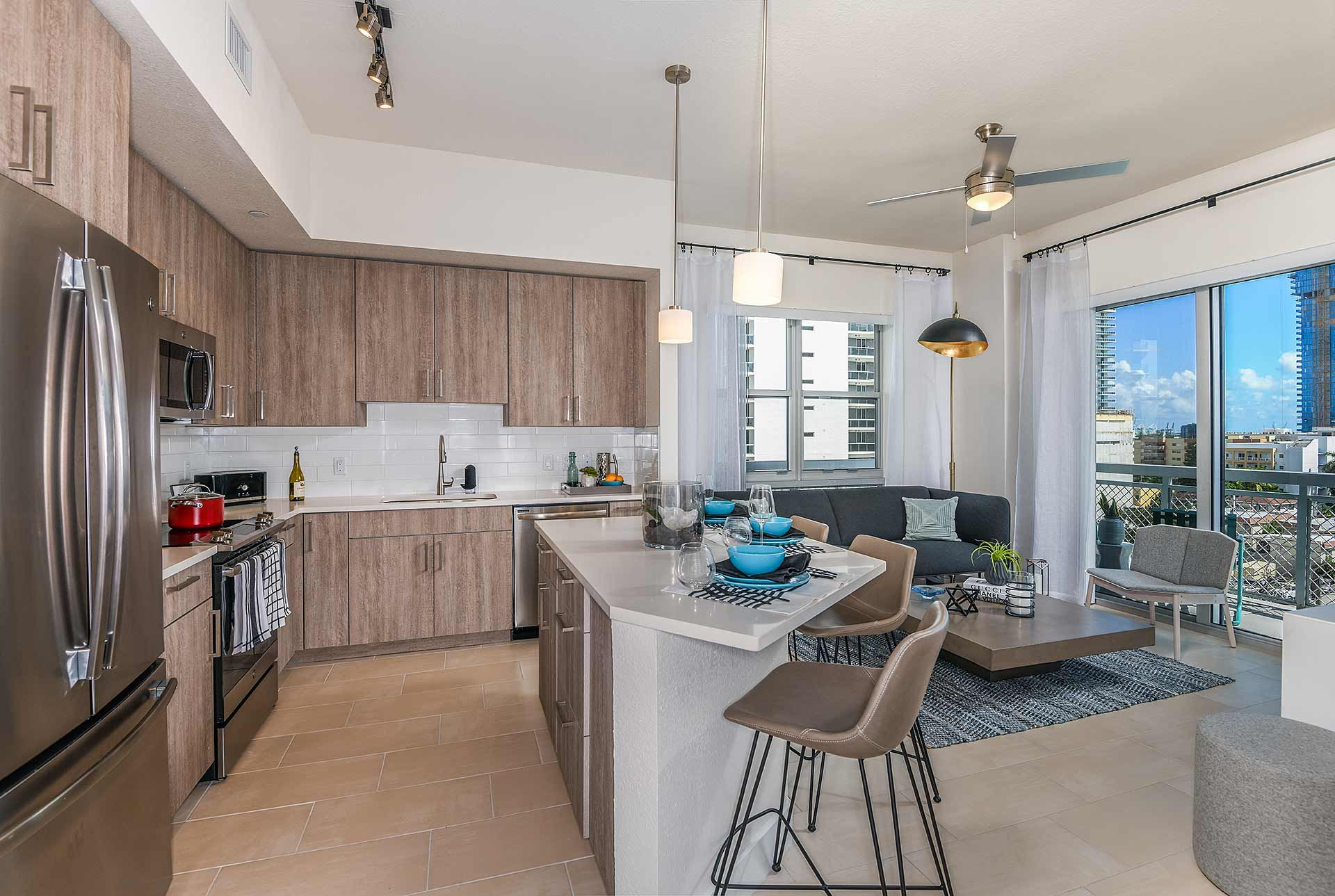 Apartment kitchen with stainless steel appliances and large bar with seating
