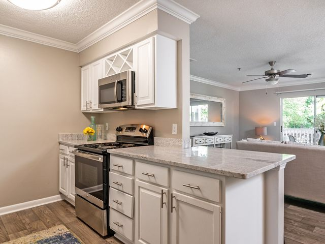 Image of kitchen with white cabinets, stainless steel appliances, and granite countertops.