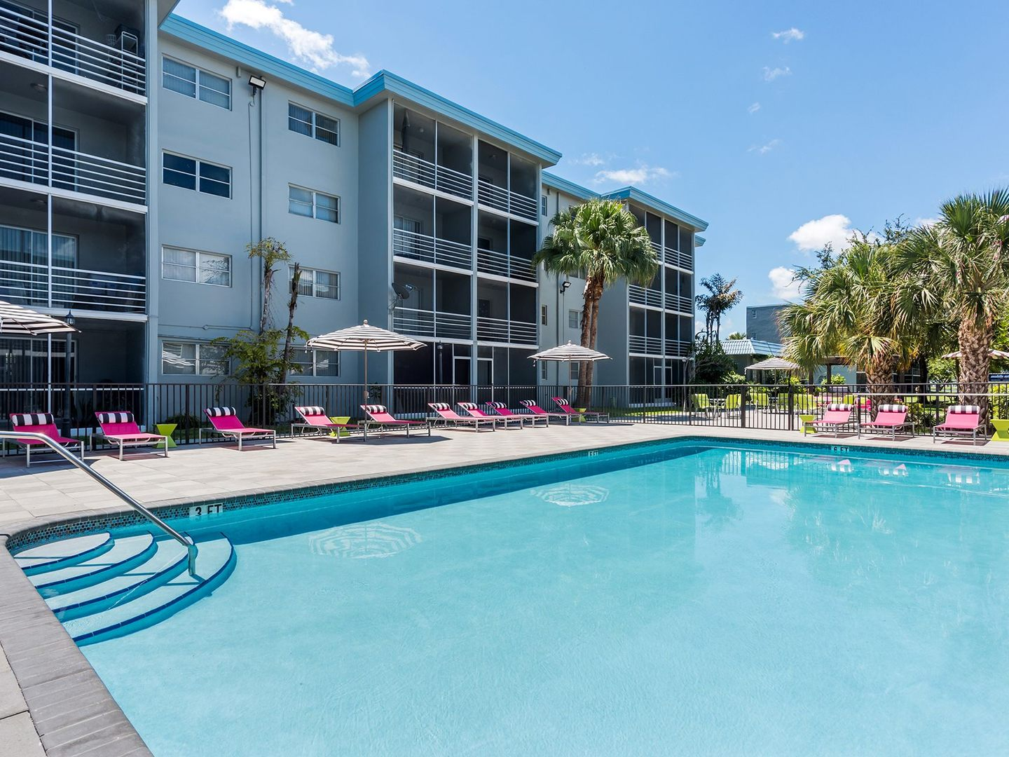 Swimming pool with lounge chairs and view of apartment building