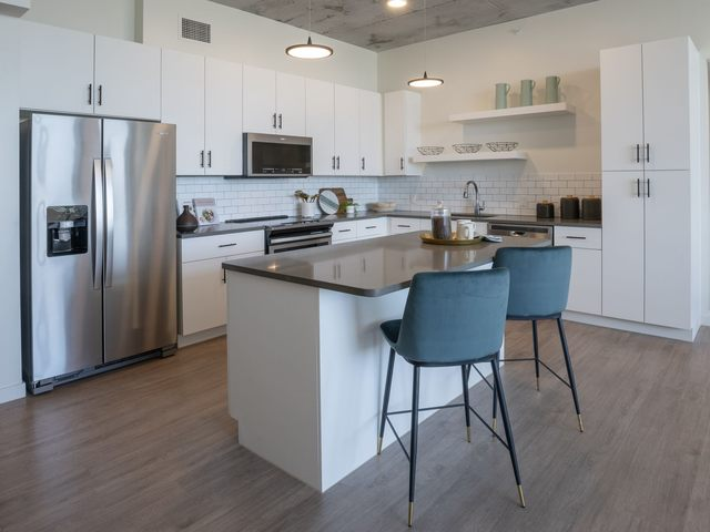 Apartment Kitchen area with seating, stainless steel appliances, and bar area
