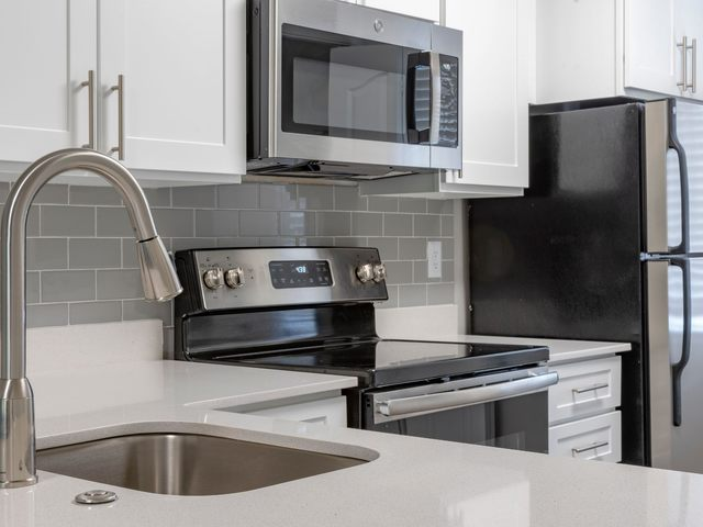Apartment kitchen with stainless steel appliances, white cabinetry, and quartz countertops