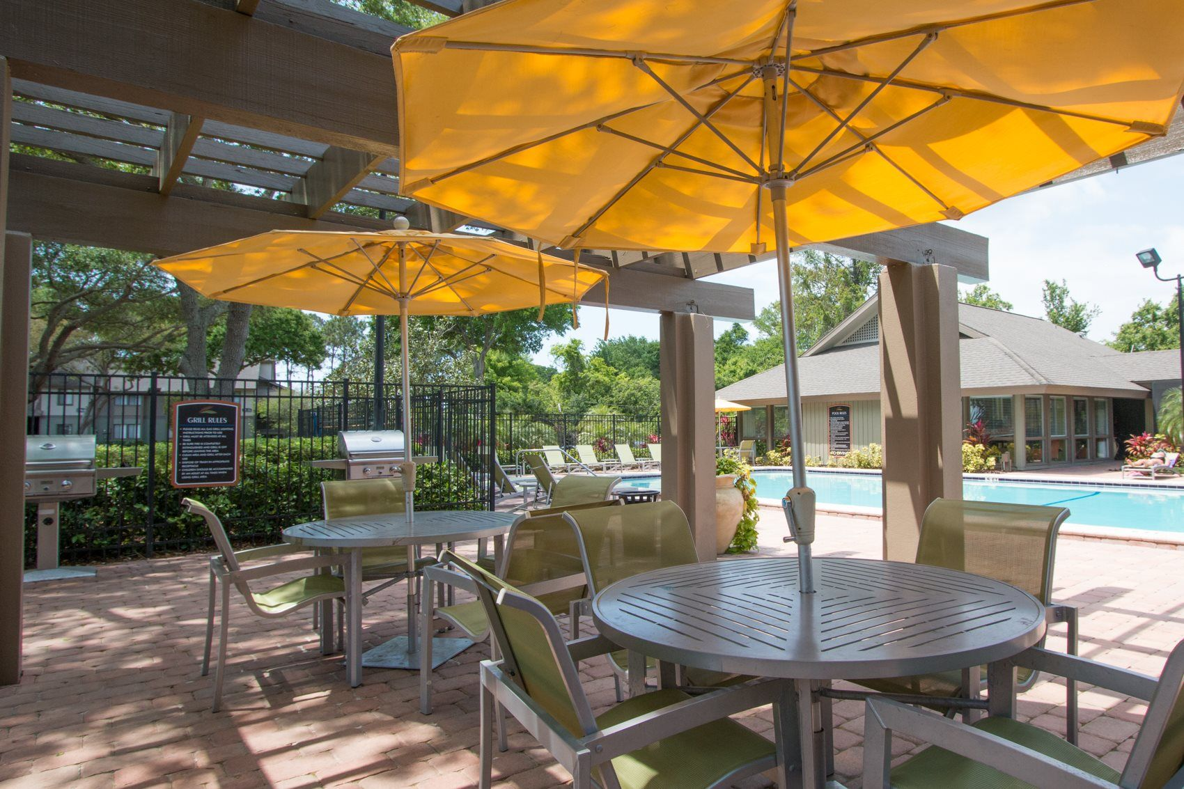 Poolside grilling area with stainless steel grills and tables and chairs