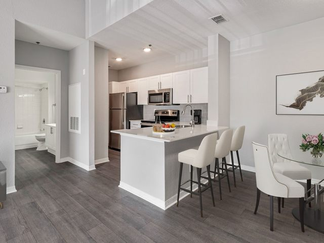 Apartment living and dining area with seating and view of kitchen