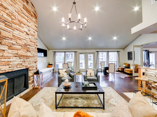 clubhouse with a fireplace, seating, and televisions
