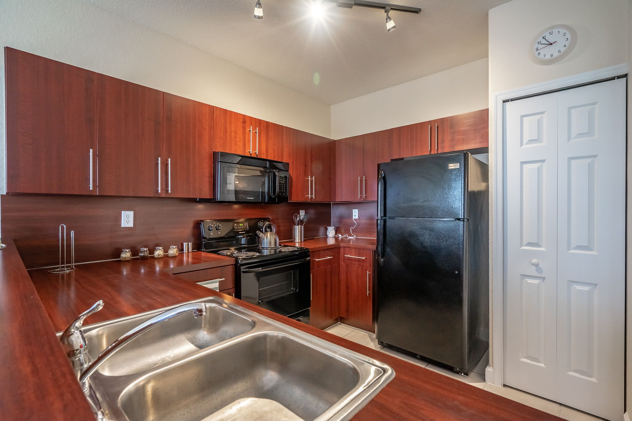 Apartment kitchen with black appliances and dark cabinetry
