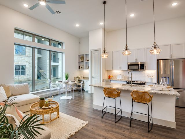 Apartment living area with view of kitchen and dining area