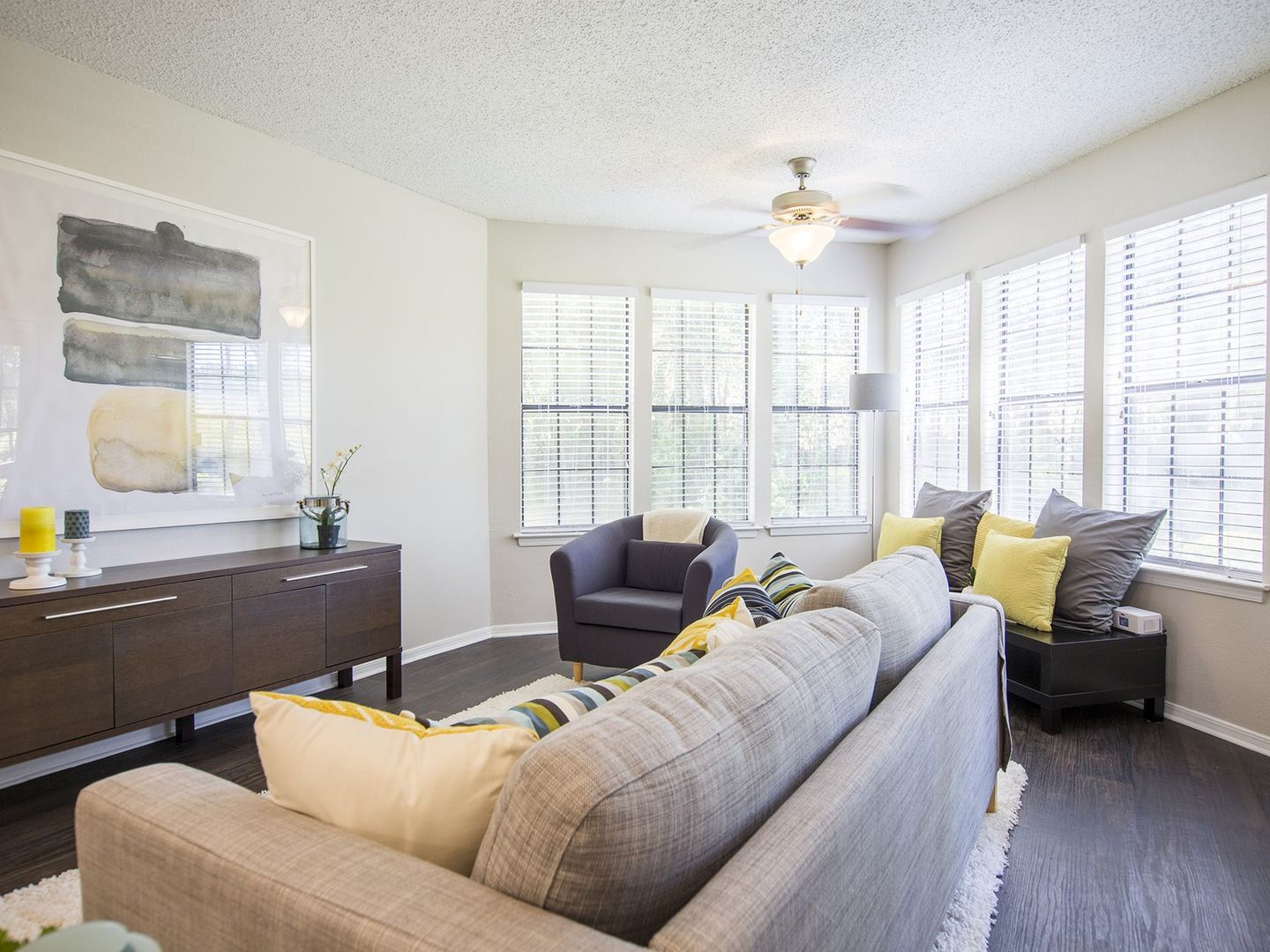 Living room with bright natural lighting, modern furnishings, and a ceiling fan.
