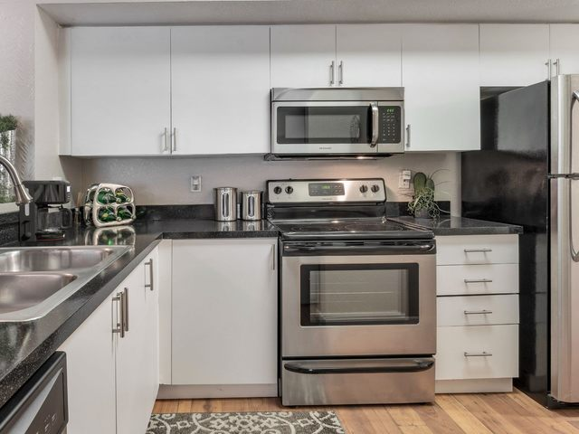 Apartment kitchen with stainless steel appliances and white cabinetry