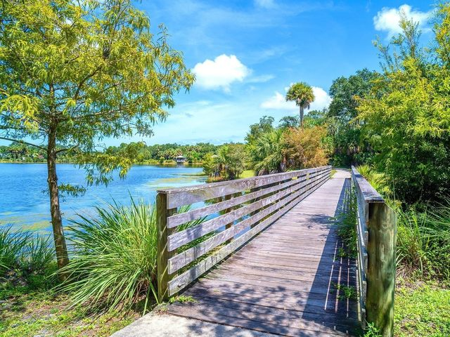 Wooden bridge alongside community lake surrounded by lush greenery.