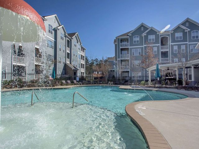 Swimming pool with water feature surrounded by deck with seating and view of apartment buildings