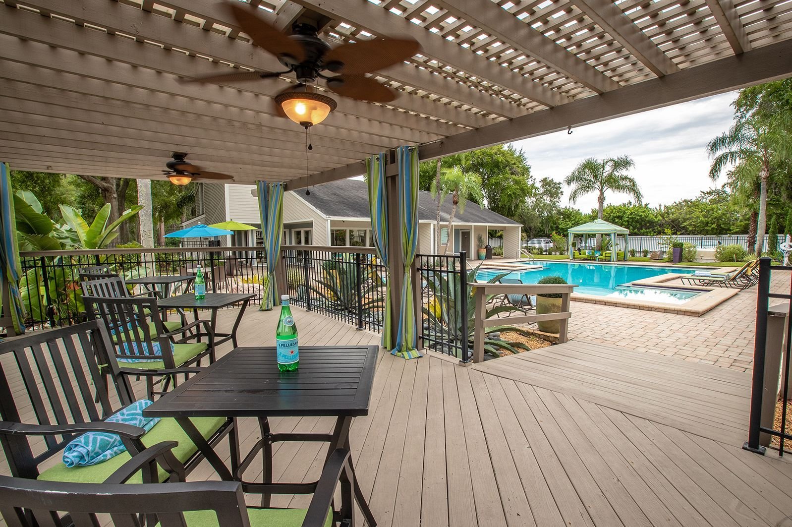 Poolside covered lounge area with tables and chairs