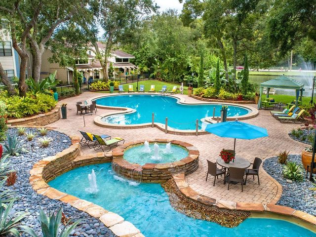 Aerial view of swimming pool and sundeck with lounge chairs and picnic areas.